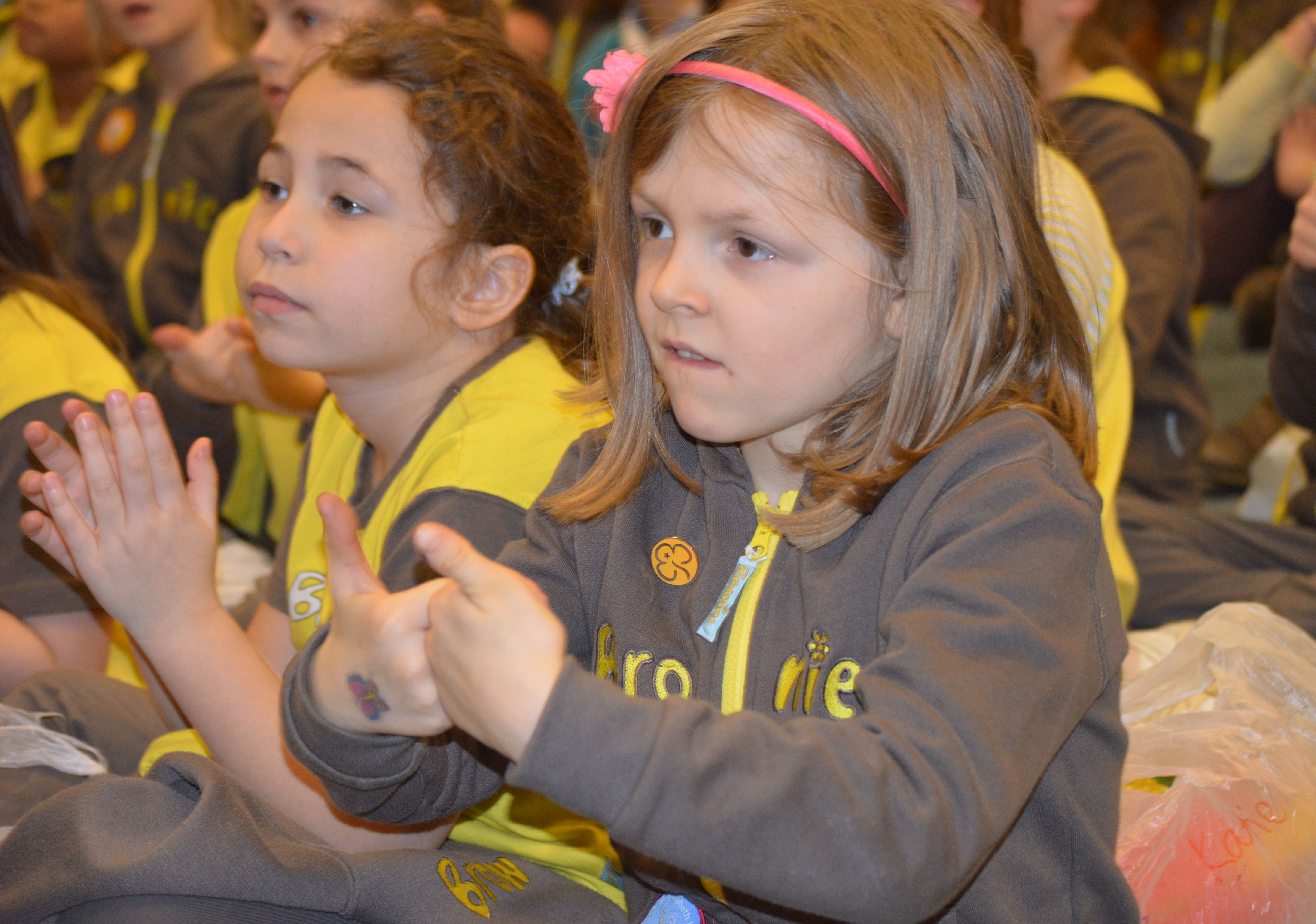 Two brownie guides taking part in sign2sing.